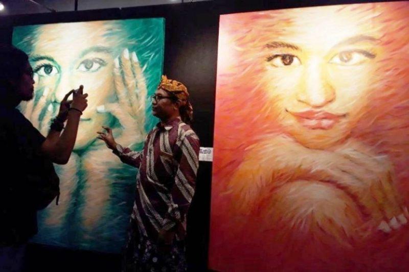Andri Wintarso pelukis realis wajah saat berbincang dengan pengunjung Bekasi Artpreneur. Foto: Suarapena.com
