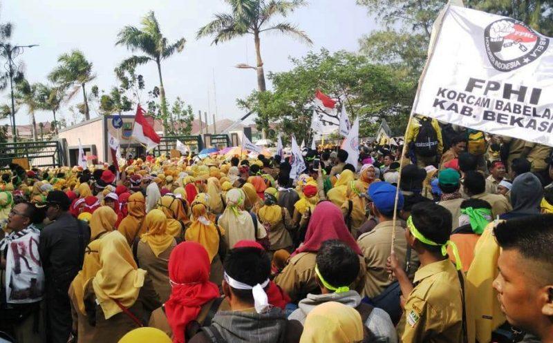 Ribuan massa tenaga honorer yang tergabung dalam Front Pembela Honorer Indonesia (FPHI) Kabupaten Bekasi saat beraksi menyuarakan sejumlah tuntutan.